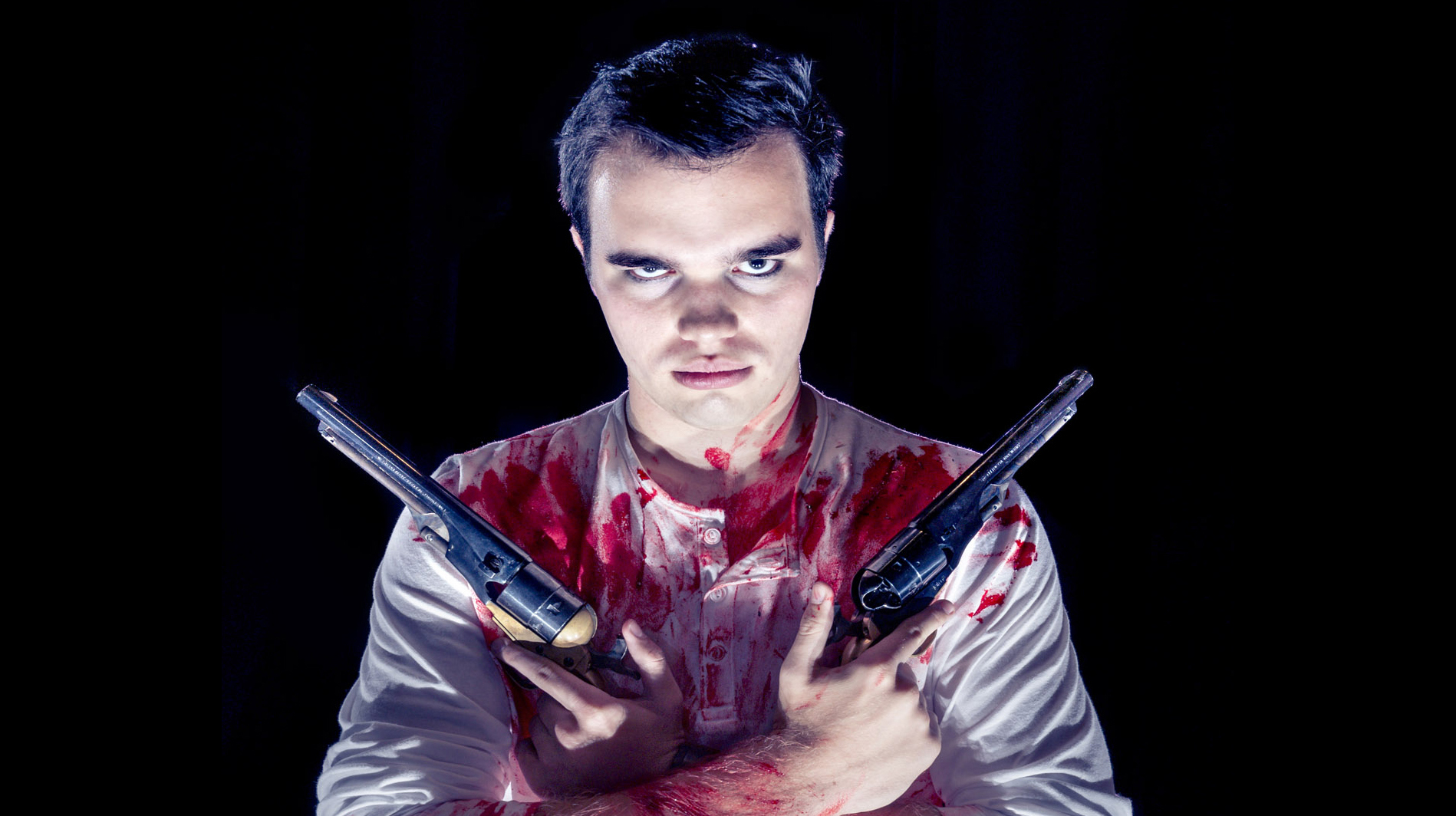 Man covered in blood, crossed arms, holding two revolvers.